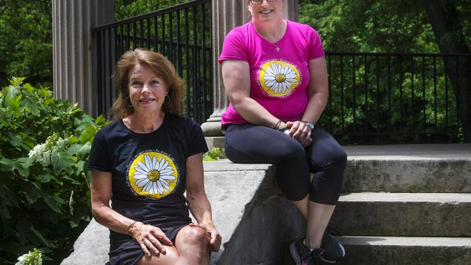 Erin Weller, left, and Julie Dailey collaborated on the design of the daisy T-shirt that is being sold as a fundraiser for frontline workers.