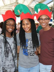 Santa's elves,  Amber Golden, Tiara Hudson, and Josh Grimes, greet people attending Christmas in the City Dec. 2 at the West Tennessee Farmers Market in downtown Jackson.