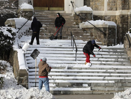 Snow shovelers clear the front steps at St. John the