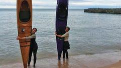 Sophie Goeks (left) and Uma Blanchard hug their kayaks