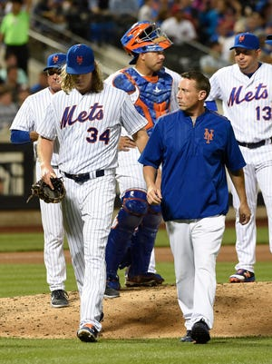 New York Mets starting pitcher Noah Syndergaard (34) is accompanied off the mound by a trainer after manager Terry Collins,  back left, removed him from a baseball game in the fifth inning, Friday, July 8, 2016, in New York.