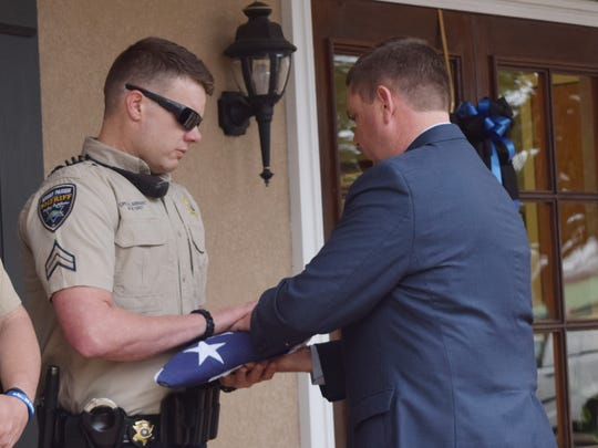 Grant Parish Sheriff Steven McCain (right) hands deputy Blake Arrant the flag which was draped over the late K9 officer Turob's casket. Arrant was Turbo's handler. A memorial service was held for Turbo at the Grant Parish Sheriff's office. Turbo was five and half and was believed to have died from a brain tumor or bleeding on the brain.