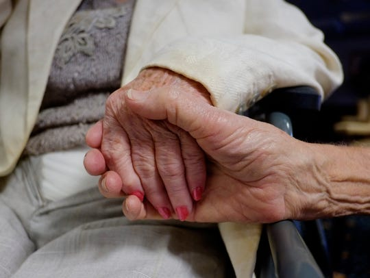 Harold Gillet, 90, holds his wife hand, Jaye, 87, who