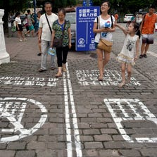 Pedestrians on Sept. 14 select a cellphone or no-cellphone lane as they walk  in southwest China's Chongqing Municipality.