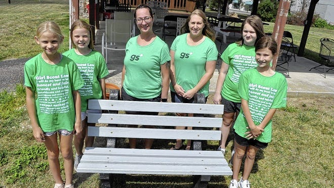 Troop leaders and members of Girl Scouts of Ohio's Heartland Troop 229 donated a bench made of recycled plastic bottle caps to the Veterans of Foreign Wars Post No. 4931 in Hilliard. With the bench are (from left): Samantha Piko, 10; Riley Needham, 10; troop leaders Penny Lonsway and Michele Piko; Allison Lonsway, 10; and Adelaide Kilbourne, 10.