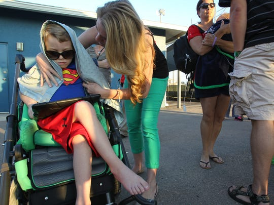 Mitochondrial Disease sufferer Gavin Lawrey, 6, is covered by mom, Brandi as the temperature cools at a baseball game Wednesday, April 23 in Fort Myers.