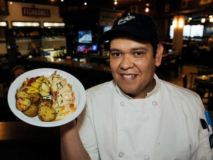 Chef Ernesto Ceja, holds a plate of Crab Stuffed Shrimp,(
