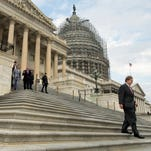 Members of Congress and aides walk down the steps of the U.S. House of Representatives.
