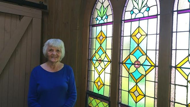 Gloria Van Dusen used the stained glass windows from St. Mary's Catholic Church, torn down in 1985, in her hot tub room. She stands by the windows Aug. 1, 2016 as she and her husband, George, prepare to leave the farm.
