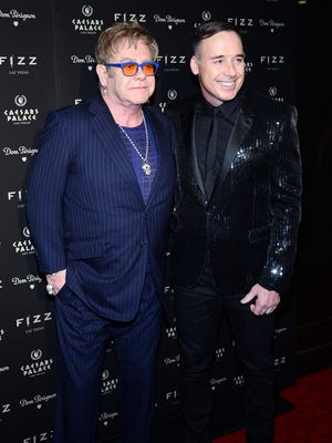 LAS VEGAS, NV - MARCH 28:  Recording artist Sir Elton John (L) and his partner, Fizz Las Vegas creative director David Furnish, arrive at the grand opening of Fizz Las Vegas inside Caesars Palace celebrating John's birthday on March 28, 2014 in Las Vegas, Nevada.  (Photo by Ethan Miller/Getty Images) ORG XMIT: 481435749 ORIG FILE ID: 481235051