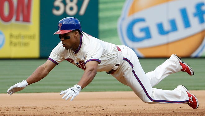 Philadelphia Phillies' Ben Revere dives into third base after reaching first and advancing on a throwing error by Los Angeles Dodgers starting pitcher Dan Haren during the sixth inning of a baseball game, Saturday, May 24, 2014, in Philadelphia. Philadelphia won 5-3. (AP Photo/Matt Slocum)