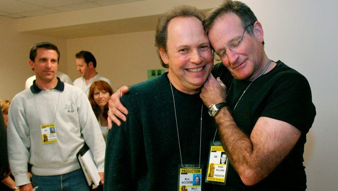 This Feb. 28, 2004 file photo shows Oscar host Billy Crystal, center, and presenter Robin Williams, right, joking around after a writers' meeting for the 76th annual Academy Awards in Los Angeles. The producer of the Emmys says that Billy Crystal will pay tribute to Robin Williams during the awards ceremony. Executive producer Don Mischer said that Crystal will honor Williams as part of the traditional ?in memoriam? segment for industry members who died during the past year. Williams was found dead by suicide in his Northern California home Aug. 11.