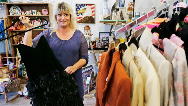 Owner Michelle Beyer has a variety of clothing items, including this feathered dress she wore to her high school prom, at Decades in downtown Lafayette. Beyer opened Decades in the June. The boutique sells vintage merchandise, including clothing and household items.