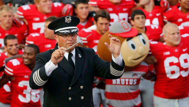 """In this Sept. 7, 2013, file photo, Ohio State University marching band director Jon Waters leads the band in """"Carmen Ohio"""" following a NCAA football game against San Diego State at Ohio Stadium in Columbus, Ohio. OSU fired Waters on Thursday amid allegations he knew about and ignored """"serious cultural issues"""" including sexual harassment."""