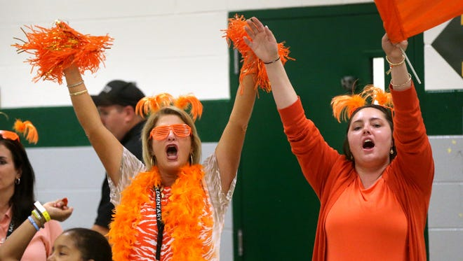 Tonya Roden and Amber Stephens both the the Walter Hill house Coraggio, cheer during a rally where 3rd - 5th grader drew to see what house they will be a part of during their time at the school on Monday August 11, 2014.