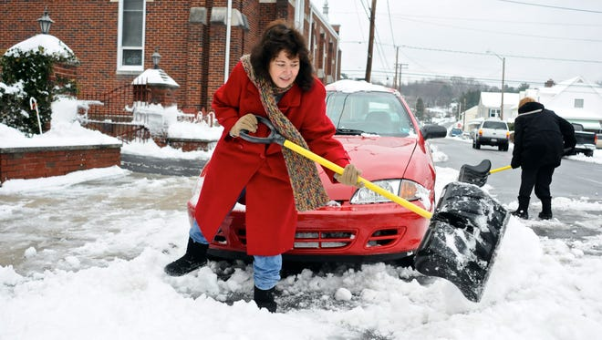Kim Weiss, of Saint Clair, Pa., front, helps shovel out the car of her friend Lucy Fox, back right, Saint Clair, Pa.  Cleanup continued after a winter storm dropped several inches of snow and created tricky travel conditions in the Northeast.