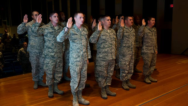 """Airmen take the Oath of Enlistment during a reenlistment ceremony in December 2013, shortly after the Air Force deleted a clause allowing airmen to omit """"so help me God,"""" from the oath."""
