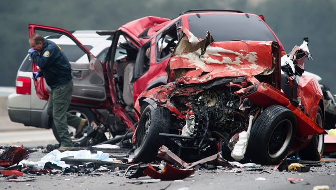 Officials investigate the scene of a multiple vehicle accident where six people were killed on the westbound Pomona Freeway in Diamond Bar, Calif., on Sunday morning.