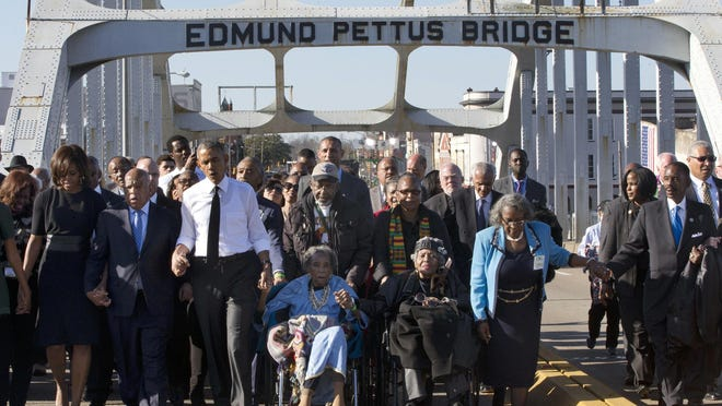 "FILE - In this March 7, 2015, file photo, singing ""We Shall Overcome,"" President Barack Obama, third from left, walks holding hands with Amelia Boynton, who was beaten during ""Bloody Sunday,"" as they and the first family and others including Rep. John Lewis, D-Ga, left of Obama, walk across the Edmund Pettus Bridge in Selma, Ala., for the 50th anniversary of ""Bloody Sunday,"" a landmark event of the civil rights movement. Some residents in the landmark civil rights city of Selma, Ala., are among the critics of a bid to rename the historic bridge where voting rights marchers were beaten in 1965."