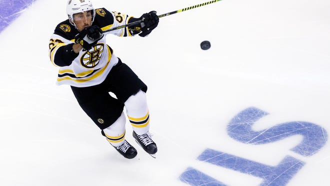Boston Bruins left wing Brad Marchand (63) watches the puck during first-period NHL hockey Stanley Cup qualifying round game action against the Washington Capitals in Toronto, Sunday, Aug. 9, 2020.