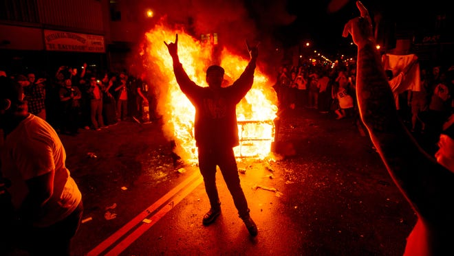 A man celebrates in front of a burning couch in the Mission district after the San Francisco Giants beat the Kansas City Royals to win the World Series on Wednesday, Oct. 29, 2014, in San Francisco.