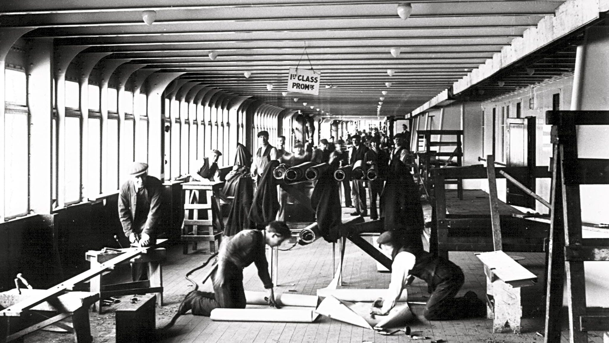 Fitting out the Queen Mary continued through May of 1936. This image shows workers installing the teak in the first-class section of the ship's enclosed promenade deck.