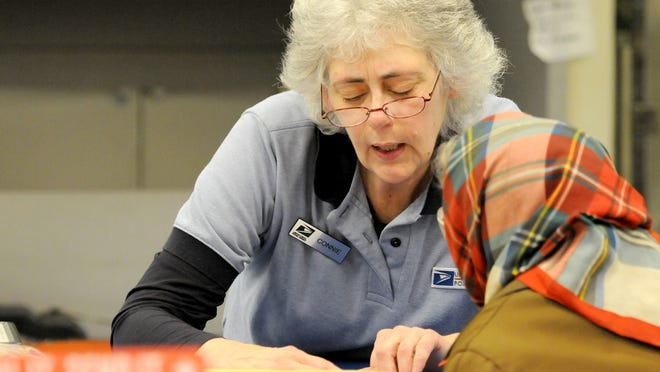 Connie Au works the counter at Mansfield Post Office main office on Diamond Street on Thursday.