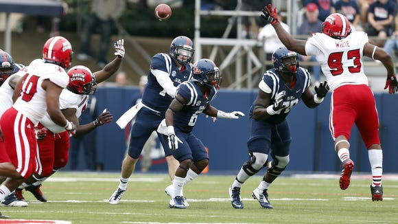 Mississippi quarterback Bo Wallace (14) passes over his line past the defense of Louisiana-Lafayette defensive lineman Marquis White (93) during the second  quarter at an NCAA college football game at Vaught-Hemingway Stadium in Oxford, Miss., Saturday, Sept. 13, 2014. (AP Photo/Rogelio V. Solis)