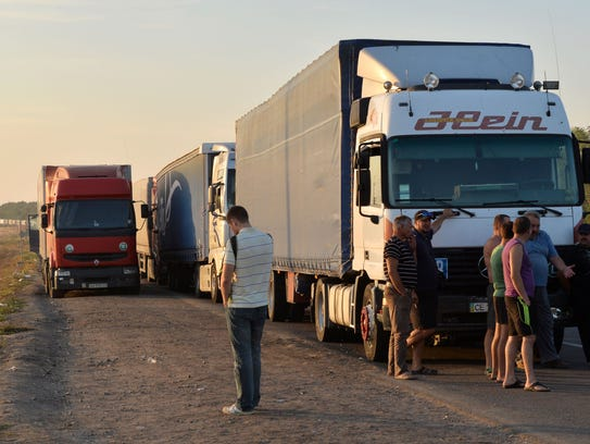 Truck drivers gather next to their trucks near a border