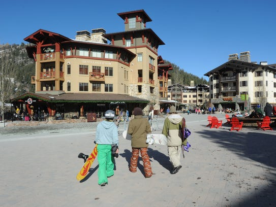 Three snowboarders head to the Village at Squaw Valley.