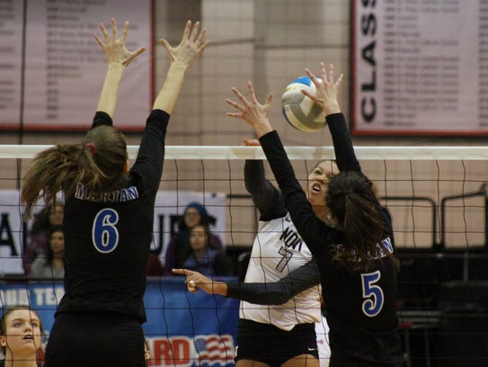 Marian's Maddie Dowd (5) blocks a kill attempt by Novi's
