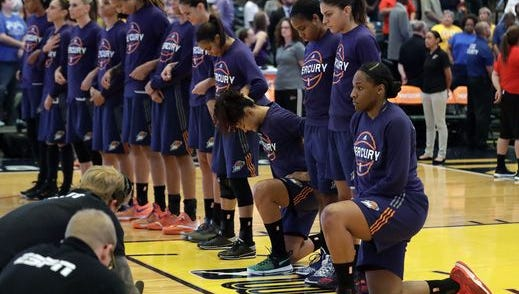 Phoenix Mercury players Kelsey Bone (right) and Mistie Bass kneel during the National Anthem Wednesday night before the WNBA first-round playoff game with the Indiana Fever in Indianapolis.
