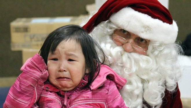 Alaina David, 2, cries while having her photo taken with Santa.