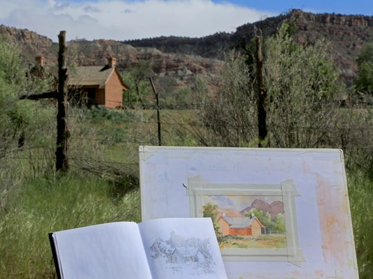 Roland Lee displays his sketch book alongside a painting in progress with his subject in the background during the Rockville Bridge Plein Air event on April 28 in Grafton.