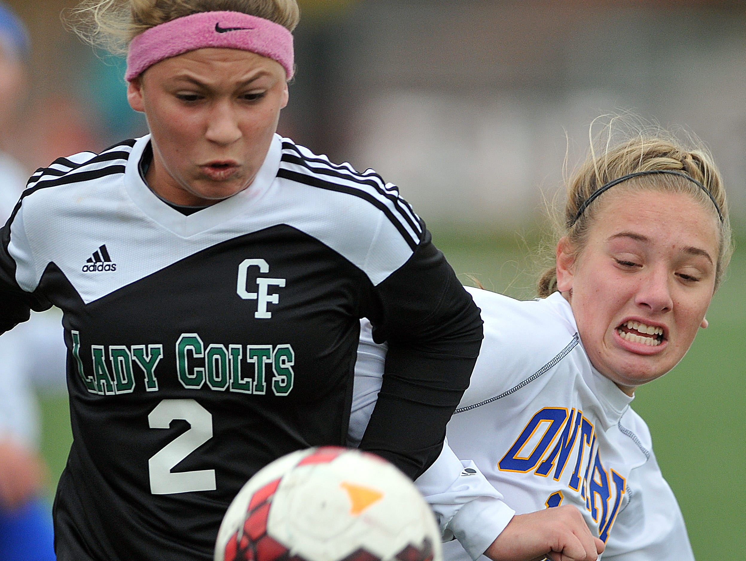 Clear Fork's Kaylin Helinski and Ontario's Amanda Nething battle for the ball during the girls soccer district championships Saturday at Ashland High School.