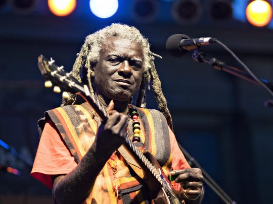 A member of the Sierra Leone Refugee All-Stars plays guitar during the Iowa Soul Festival on the Main Stage in the Pentacrest on Sept. 19, 2014.