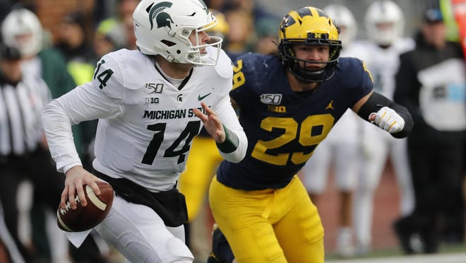 Michigan State Spartans quarterback Brian Lewerke (14) scrambles against Michigan Wolverines linebacker Jordan Glasgow (29) in the second half at Michigan Stadium.