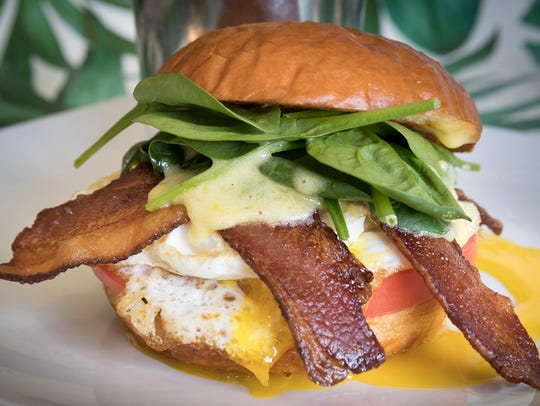 The Breakfast Sandwich at Meridian Cafe includes fried eggs with a splash of hollandaise sauce, applewood bacon, spinach, sliced tomato and cheddar on a brioche bun.