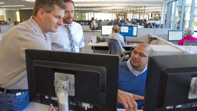 Director of infrastructure Garret Sisco, left, explains a procedure to ensure cyber security to Christopher Smith, software craftsman lead, and compliance manager Omari Boone (seated) at Lake Trust Credit Union in Brighton Township.