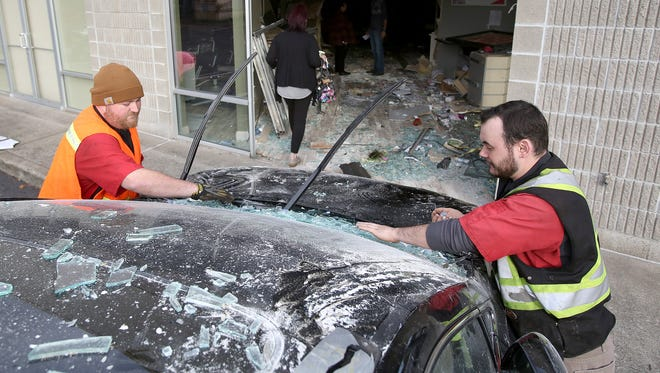 Travis Cook, left, and Alex Hoy, both with Wiltse's Towing, clean debris off of a 2015 Lexus that crashed into the Great Clips located in a shopping center in the 3400 block of Commercial Street SE on Tuesday, Nov. 3, 2015, in Salem, Ore.
