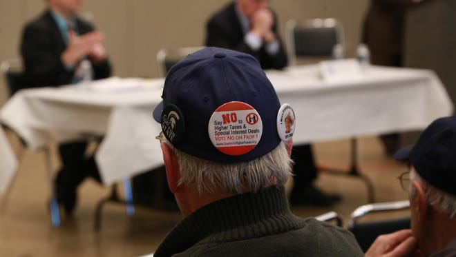 A man showing support of voting no on Proposal 1 listens as Tom McMillin, chairman of Concerned Taxpayers of Michigan, speaks about during a Proposal 1 forum held by the Oakland County Republican Party on March 25, 2015 at the Troy Community Center.