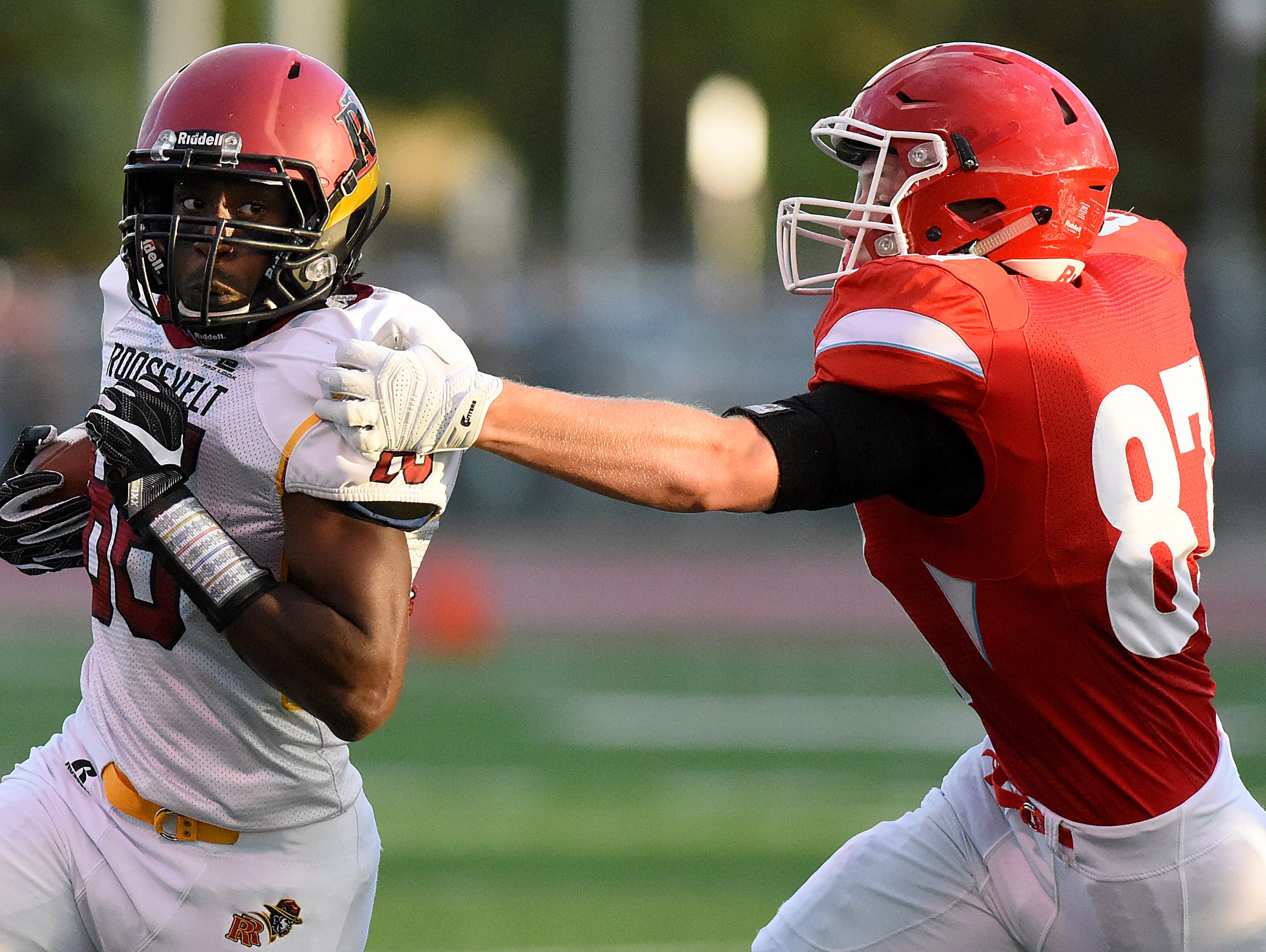 Roosevelt's Demareio Hester carries the ball while trying to get away from Lincoln's Trent Naasz during their game on Friday at Howard Wood Field.