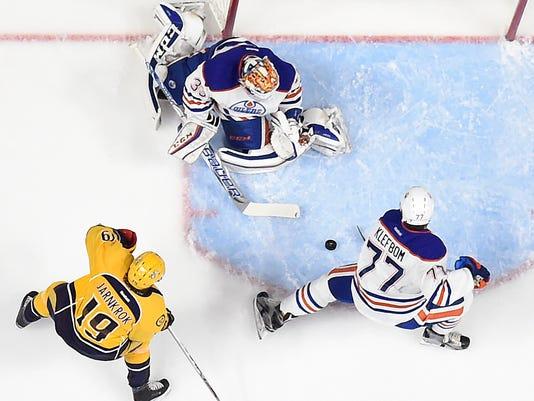 Edmonton Oilers goalie Cam Talbot (33) blocks a shot by Nashville Predators center Calle Jarnkrok (19), of Sweden, as defenseman Oscar Klefbom (77), also of Sweden, clears the puck out of the crease in the first period of an NHL hockey game Saturday, Oct. 10, 2015, in Nashville, Tenn. (AP Photo/Mark Zaleski)
