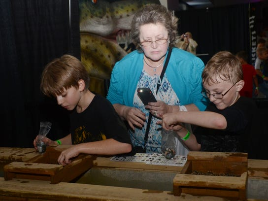 """ANI Discover the Dinosaurs Asher Carlson (left) along with his friend Damaien Nash mine for gems and fossils at Blue Star Media's """"Discover the Dinosaurs"""" exhibit held Saturday, Nov. 23, 2014 at the Alexandria Riverfront Center in downtown Alexandria. T"""