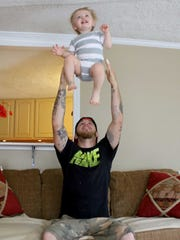 23 year-old Dillon Walker plays with his 18 month-old son Zeke, who he credits to helping keep him sober.