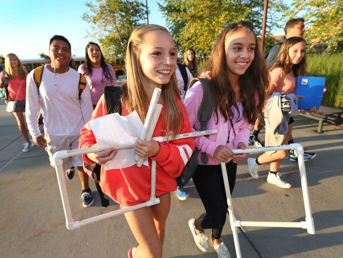 Creekside Middle School seventh-graders Chloe Meredith, left, and Marissa Ryan, both 13, carry locker components as they head to classes on the first day of school, Wednesday, August 13, 2014, as Carmel Clay Schools begin the 2014-2015 school year. The school, at 3525 W. 26th St., Carmel, has 1,600 students in grades 6-8.
