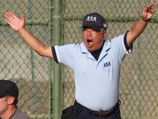 Umpire Joe Yoshimura gestures as he makes a call during a Metro softball tournament game Aug. 4, 2010.
