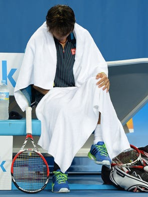Japan's Kei Nishikori rests during a break in his men's singles match against Donald Young of the USA.