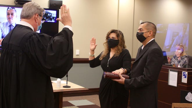 58th District Court Chief Judge Bradley Knoll swears in Juanita Bocanegra as the next 58th District Court judge as her husband Jose holds the Bible on Friday, Dec. 18, 2020.