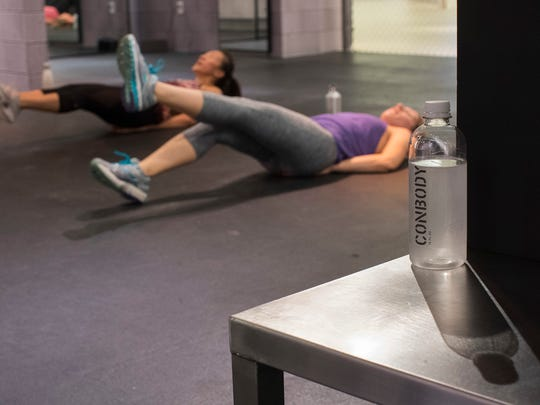 ConBody brand water rests on a bench during a workout